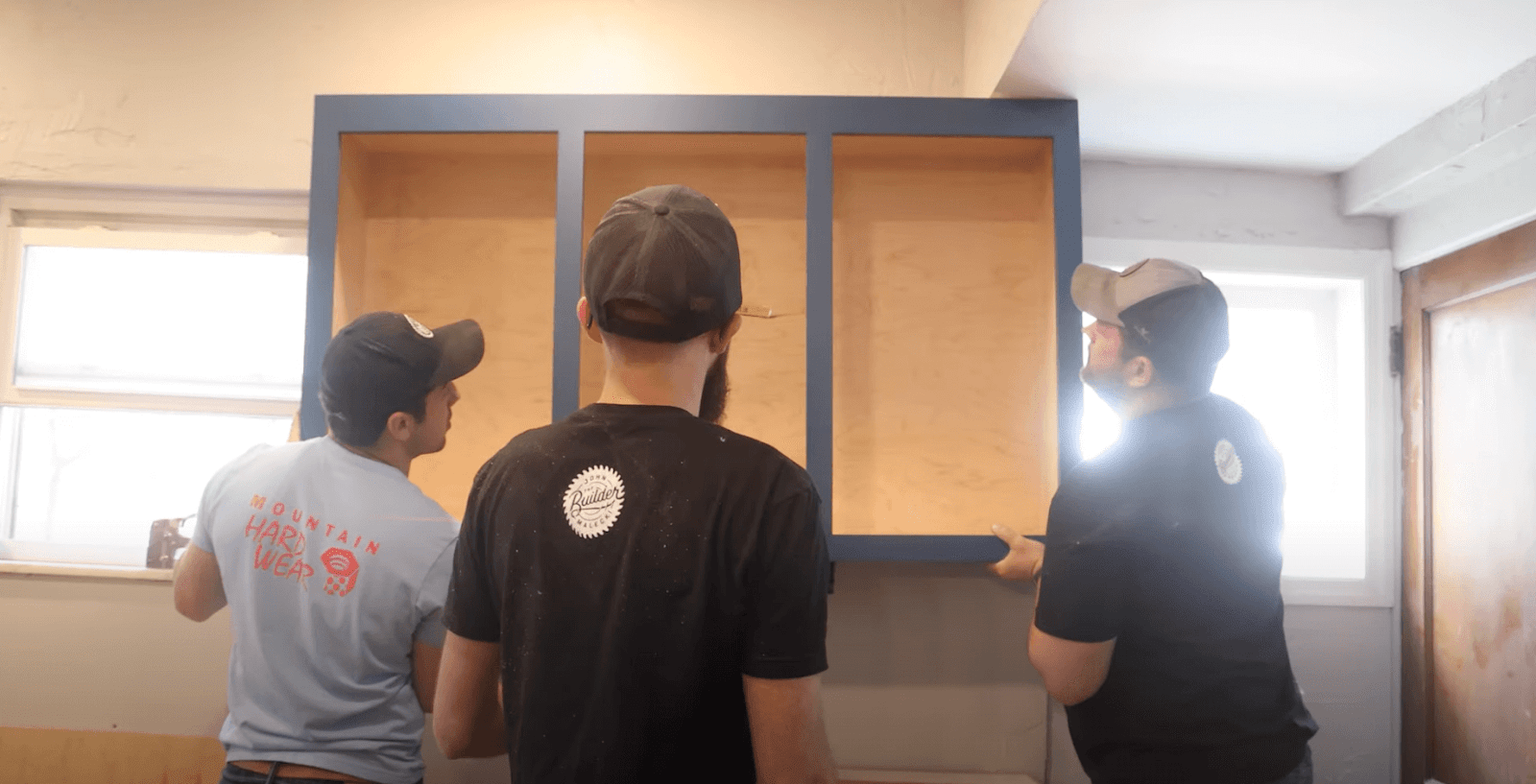John, Sam, and Jordan holding cabinets