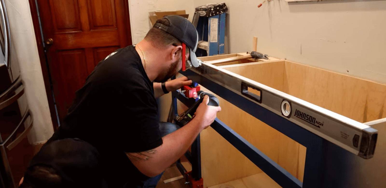 John Malecki working on a cabinet