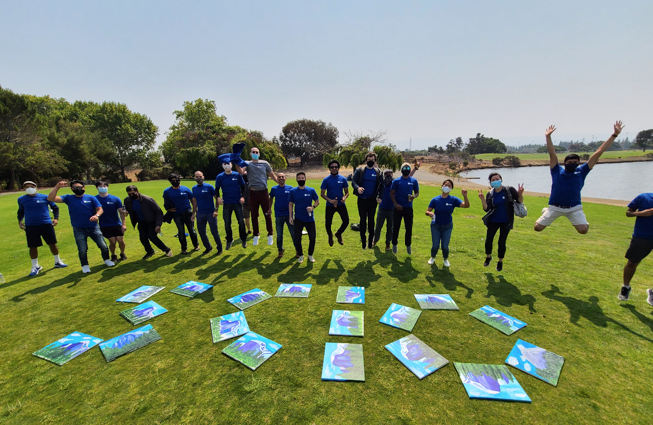 "Scio company members jumping behind a series of canvasses on grass spelling out ""SCIO"""