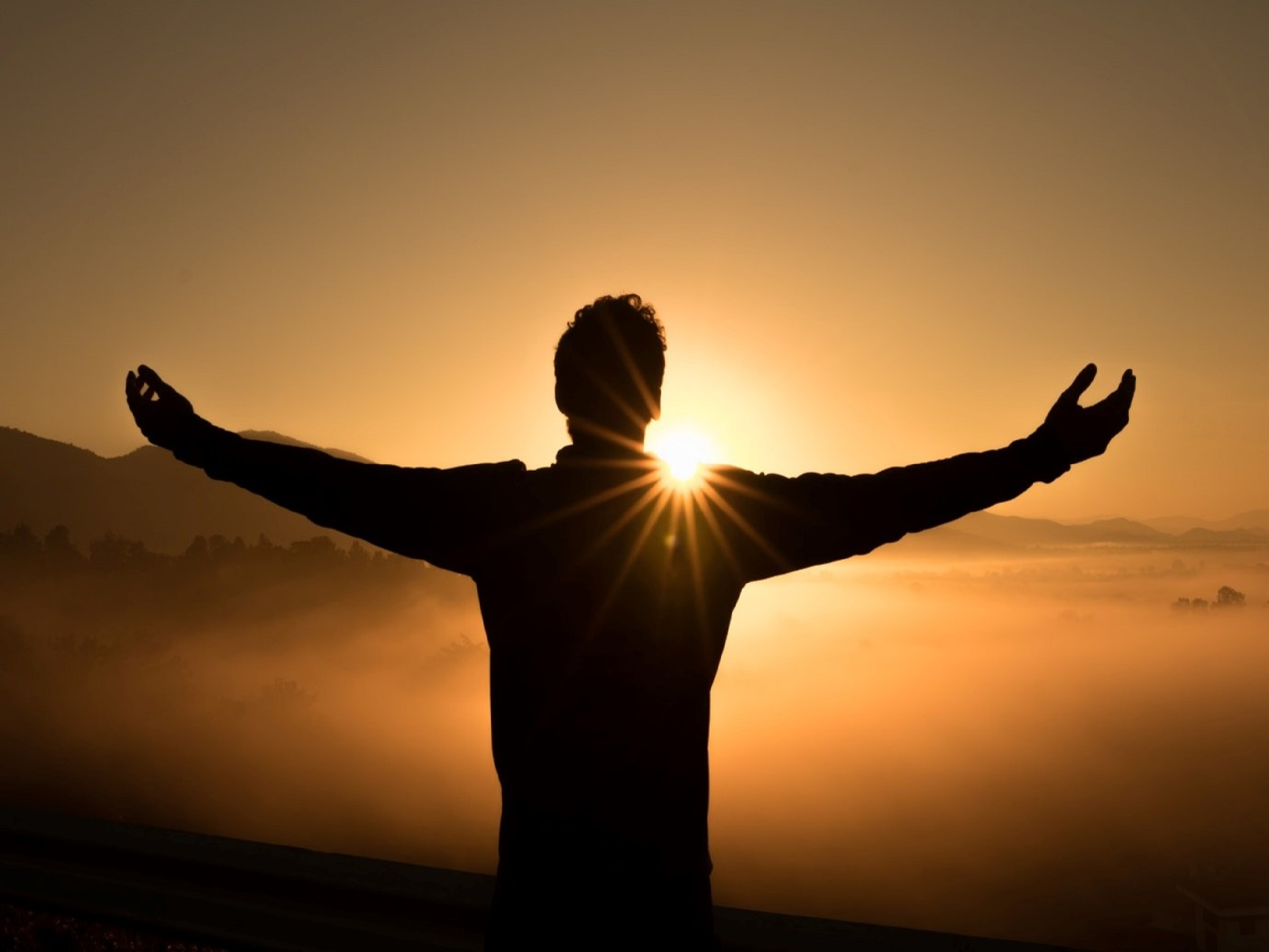 Silhouette of man in front of sunset with arms outstretched