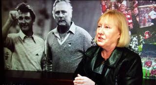 Wendy Dickinson standing in front of a screen showing her Dad Peter Taylor and his working partner Brian Clough