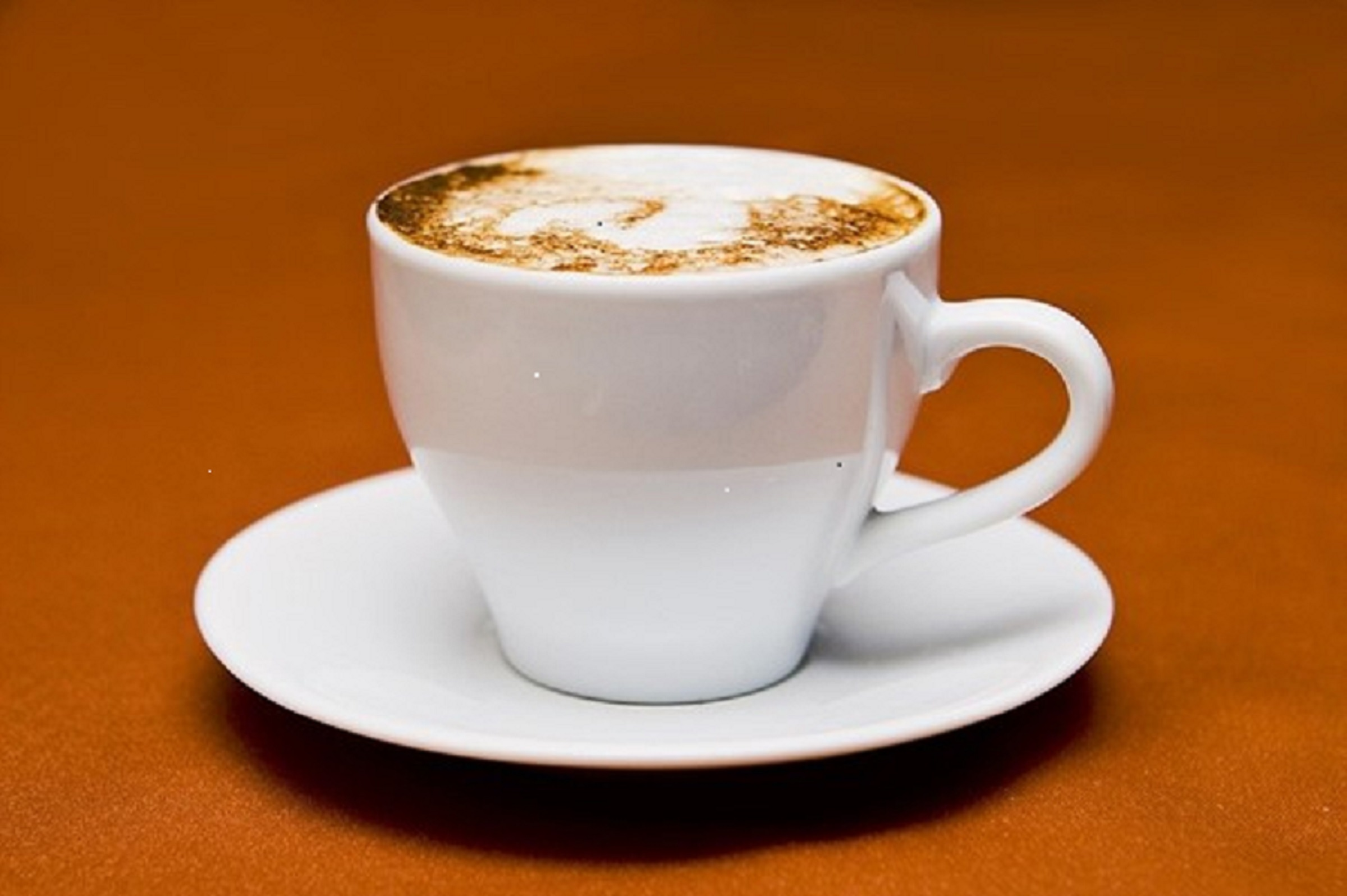 White cup of coffee on a tan background