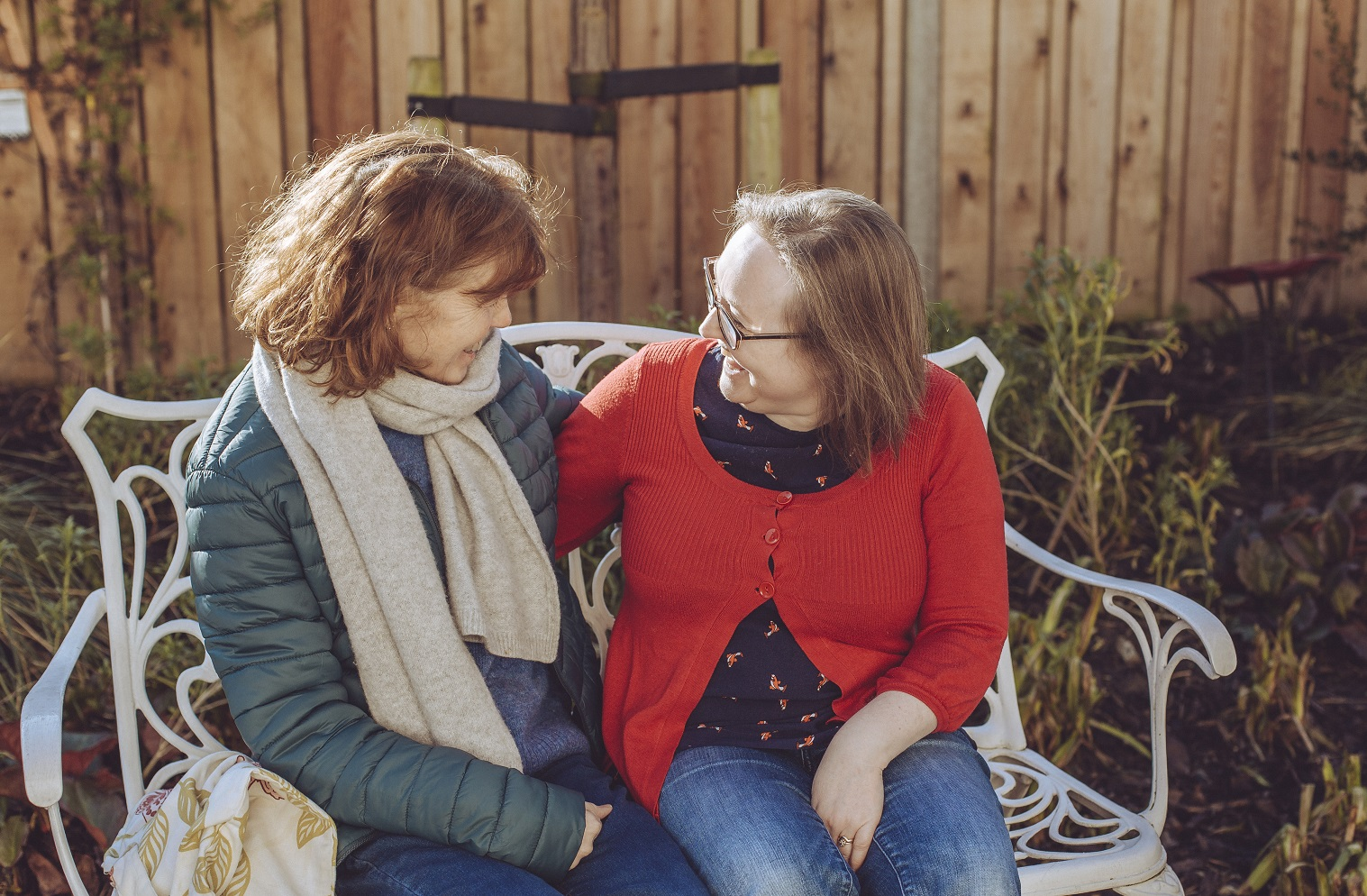 Two patients sitting on a bench, arm around each other smiling