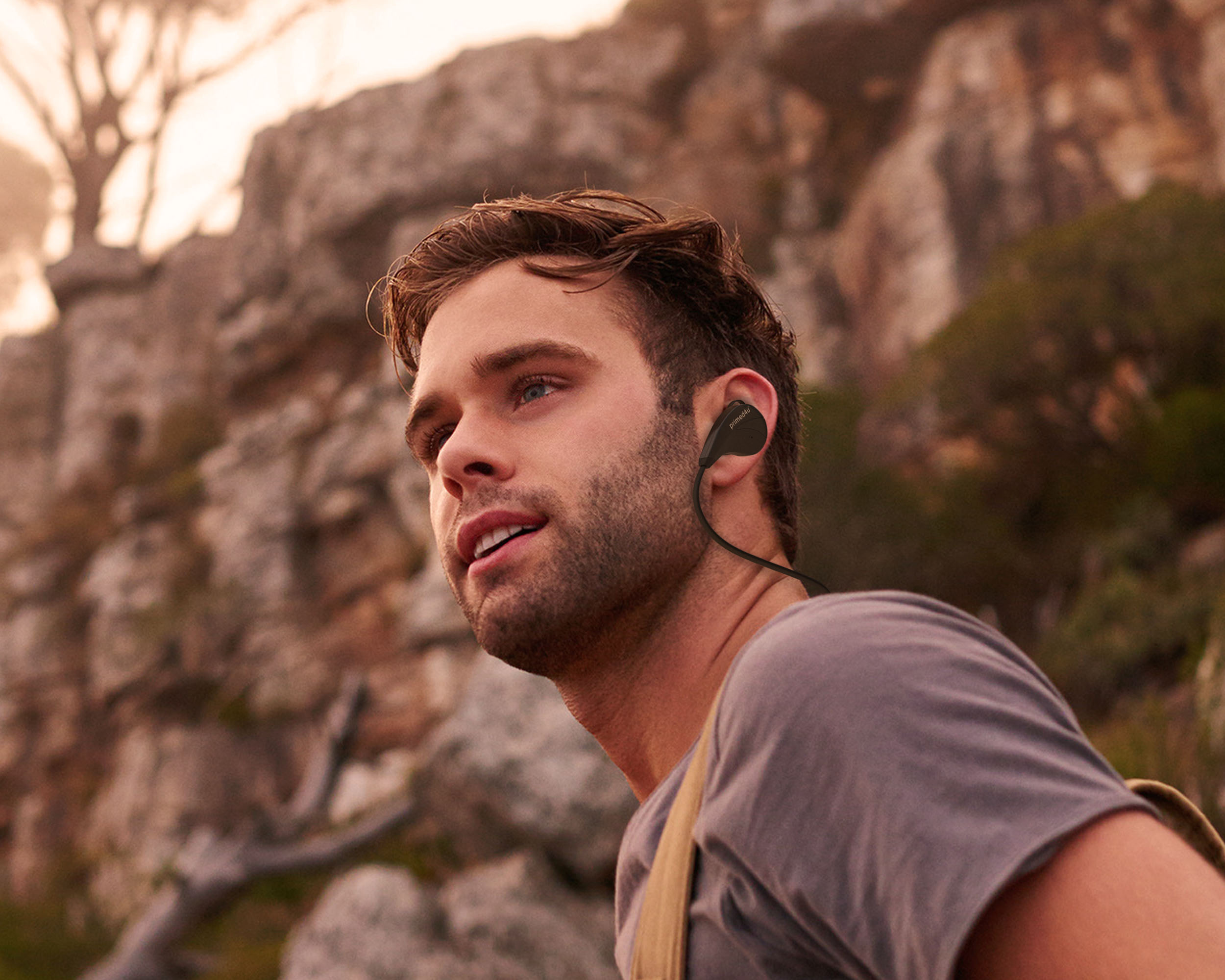 Young man hiking while wearing Primed4U headphone product