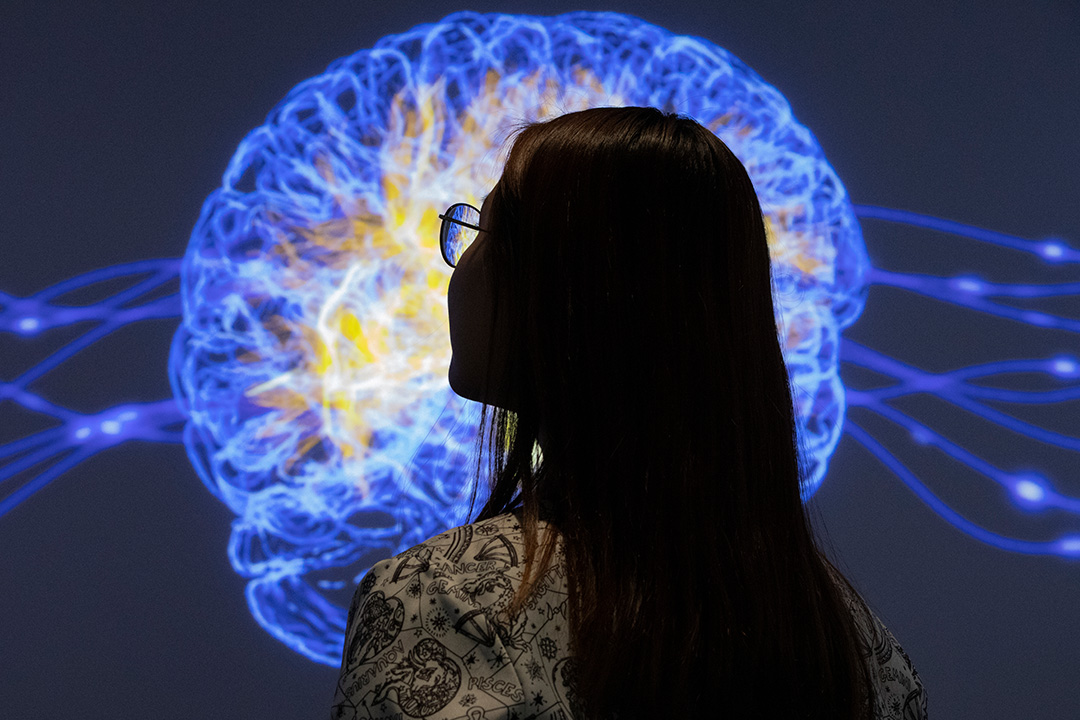 A young woman's silhouette against a screen with a computer rendered brain projected on to it.