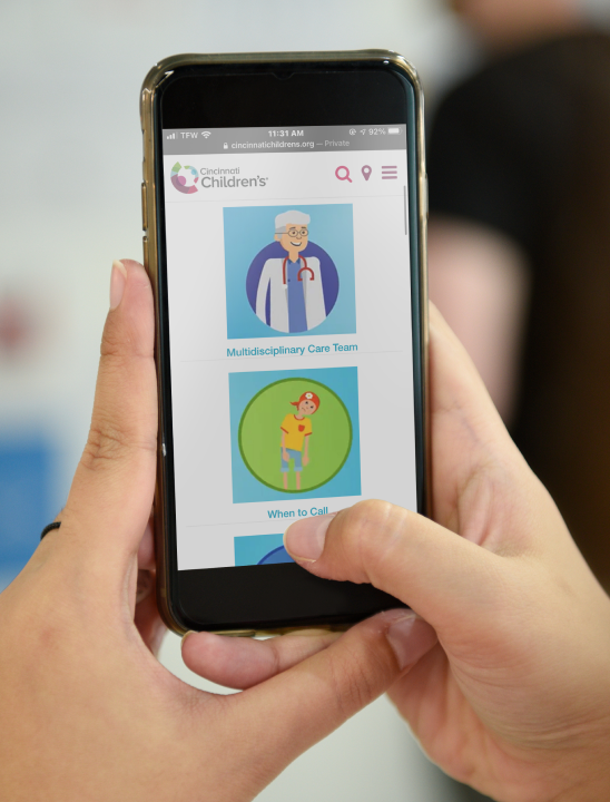 Someone using the digital version of the oncology handbook on their phone