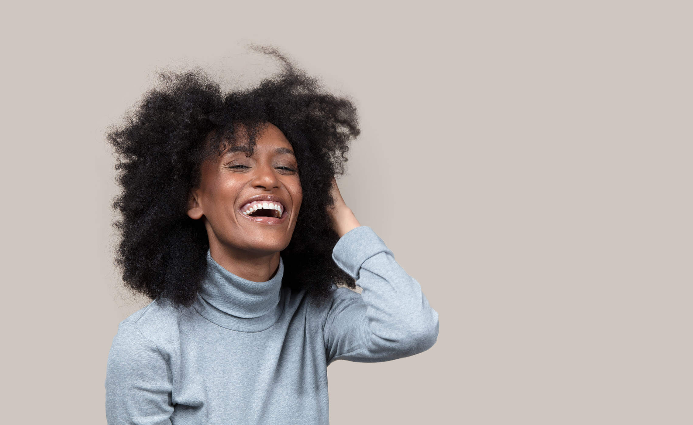Woman running hand through her hair laughing.