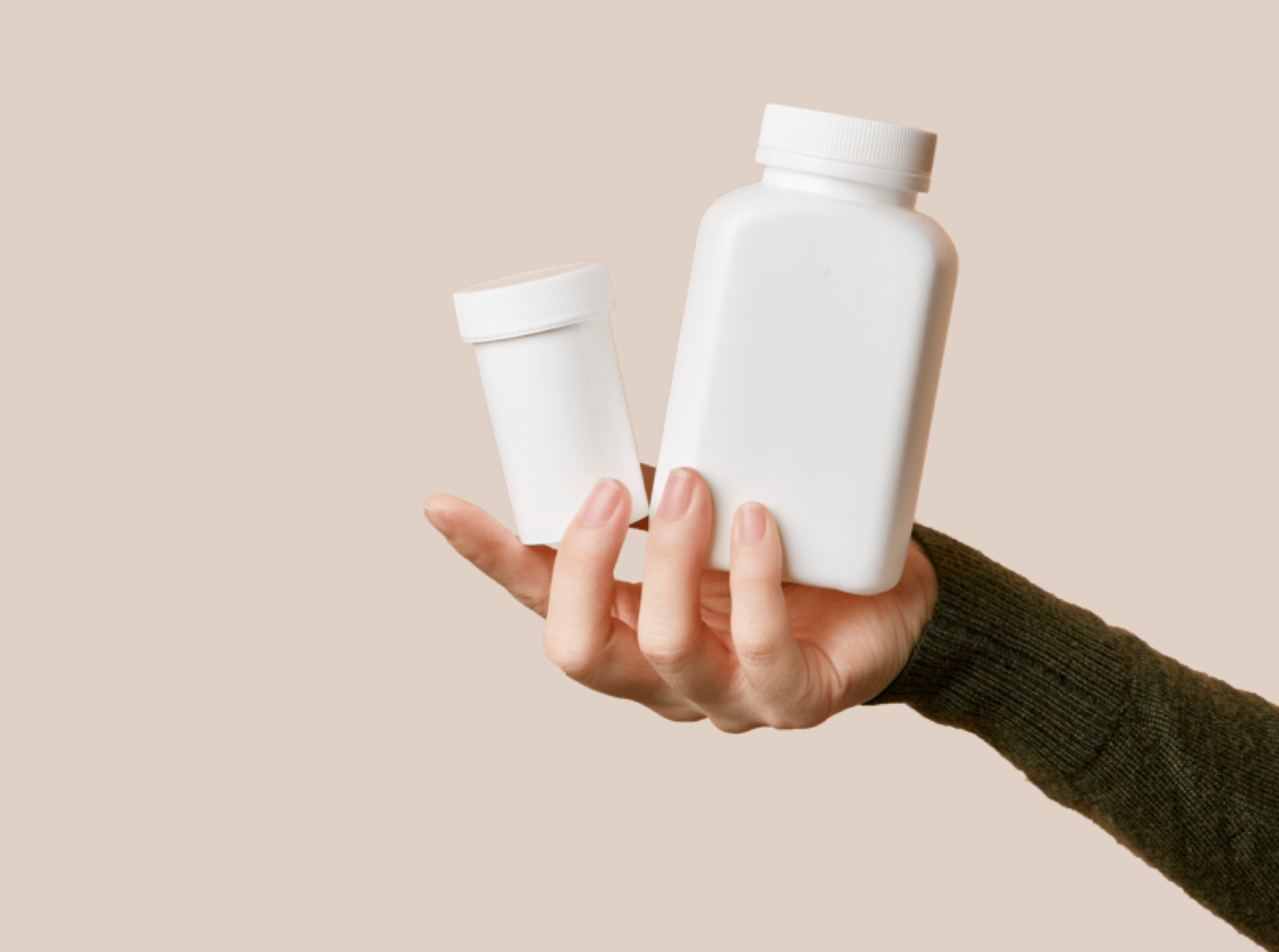 Hand holding white pill bottles.
