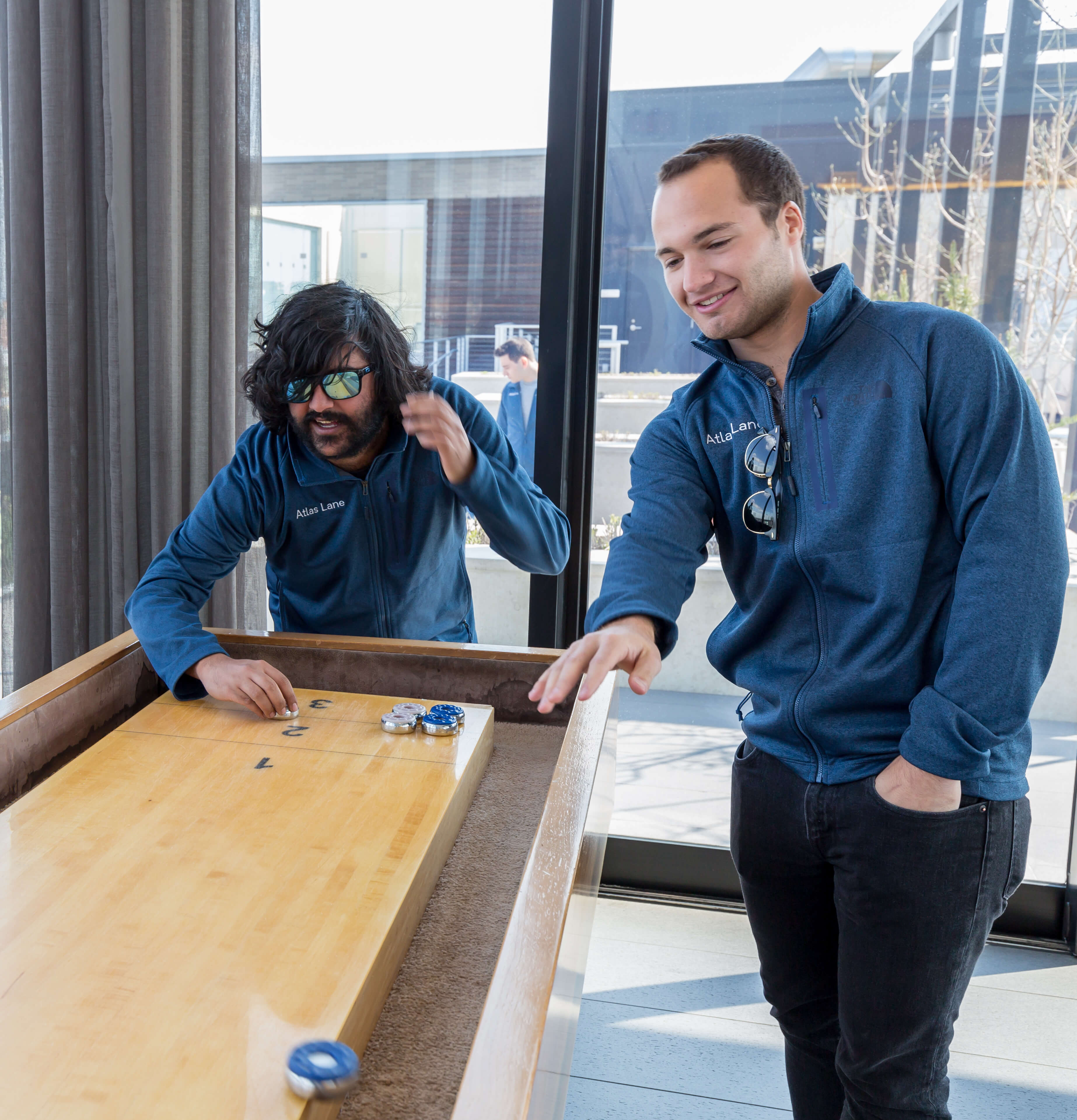 Two Atlas Lane employees playing shuffleboard together.