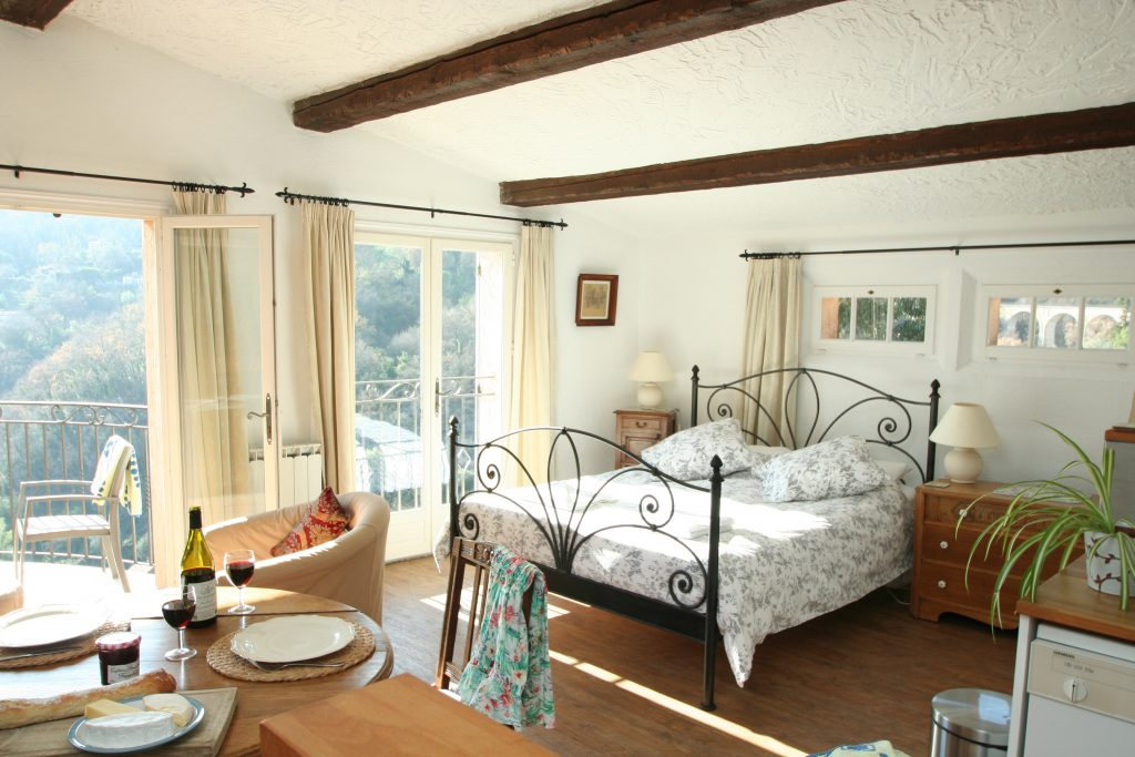 Top Studio interior with dining table and comfortable wrought iron king size bed.