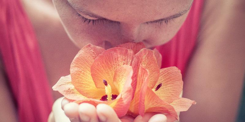 Femme sentant le parfum d'une fleur