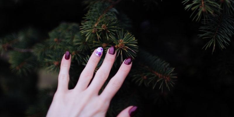 Main de femme avec du vernis violet
