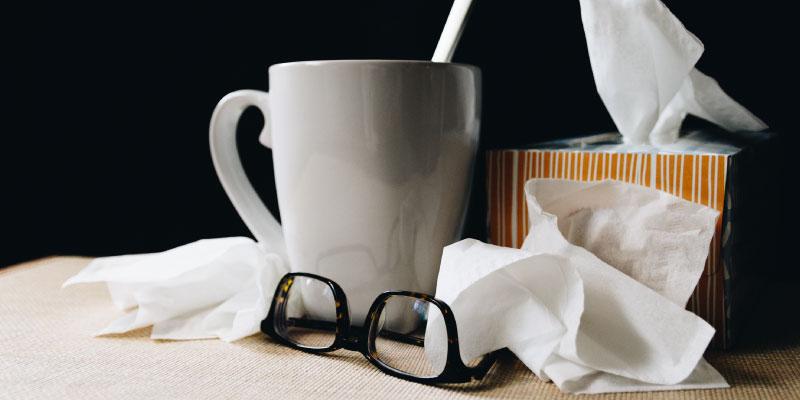 Tasse de tisane chaude entourée de mouchoirs utilisés
