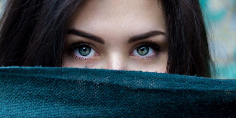Femme aux yeux verts qui cache son visage