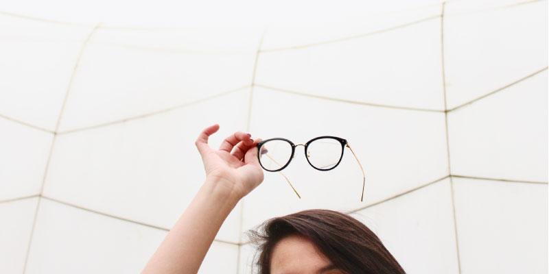 Femme qui tient des lunettes au dessus de sa tête