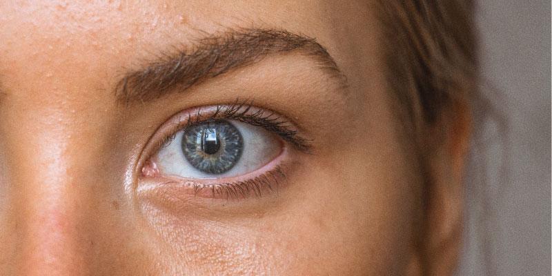 Gros plan sur un oeil avec le visage non maquillé