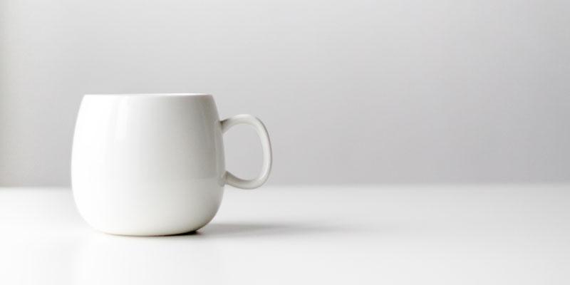 Tasse blanche sur fond gris