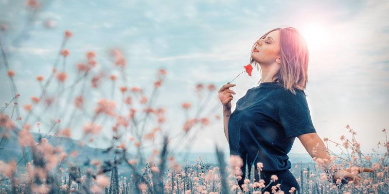 Femme au milieu d'un champs de fleurs