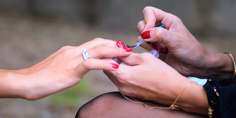Femme qui applique du vernis à ongles