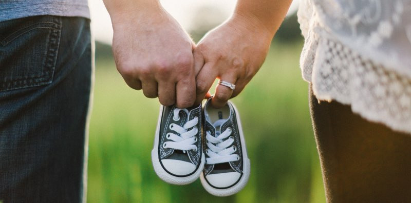 Futurs parents tenant des chaussures de bébé