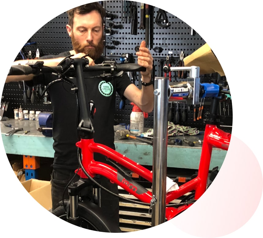 A Good Cycles employee working on a red Tern HSD
