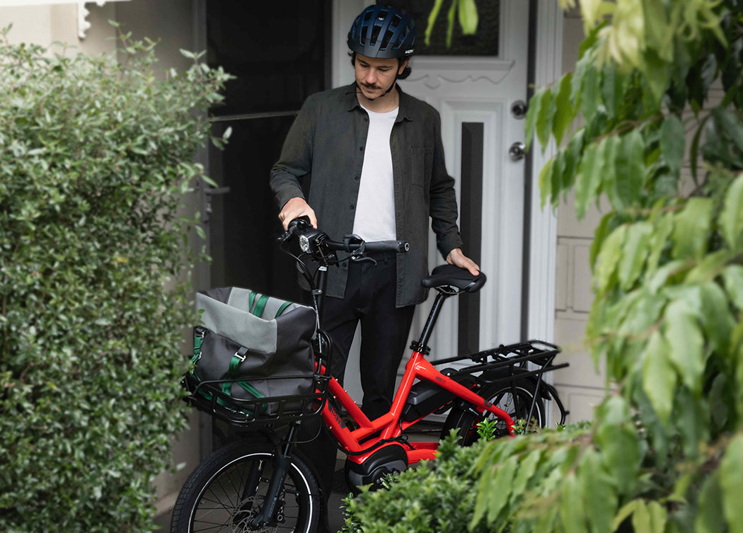 Man on the porch of his house with a red Tern HSD electric commuting bike