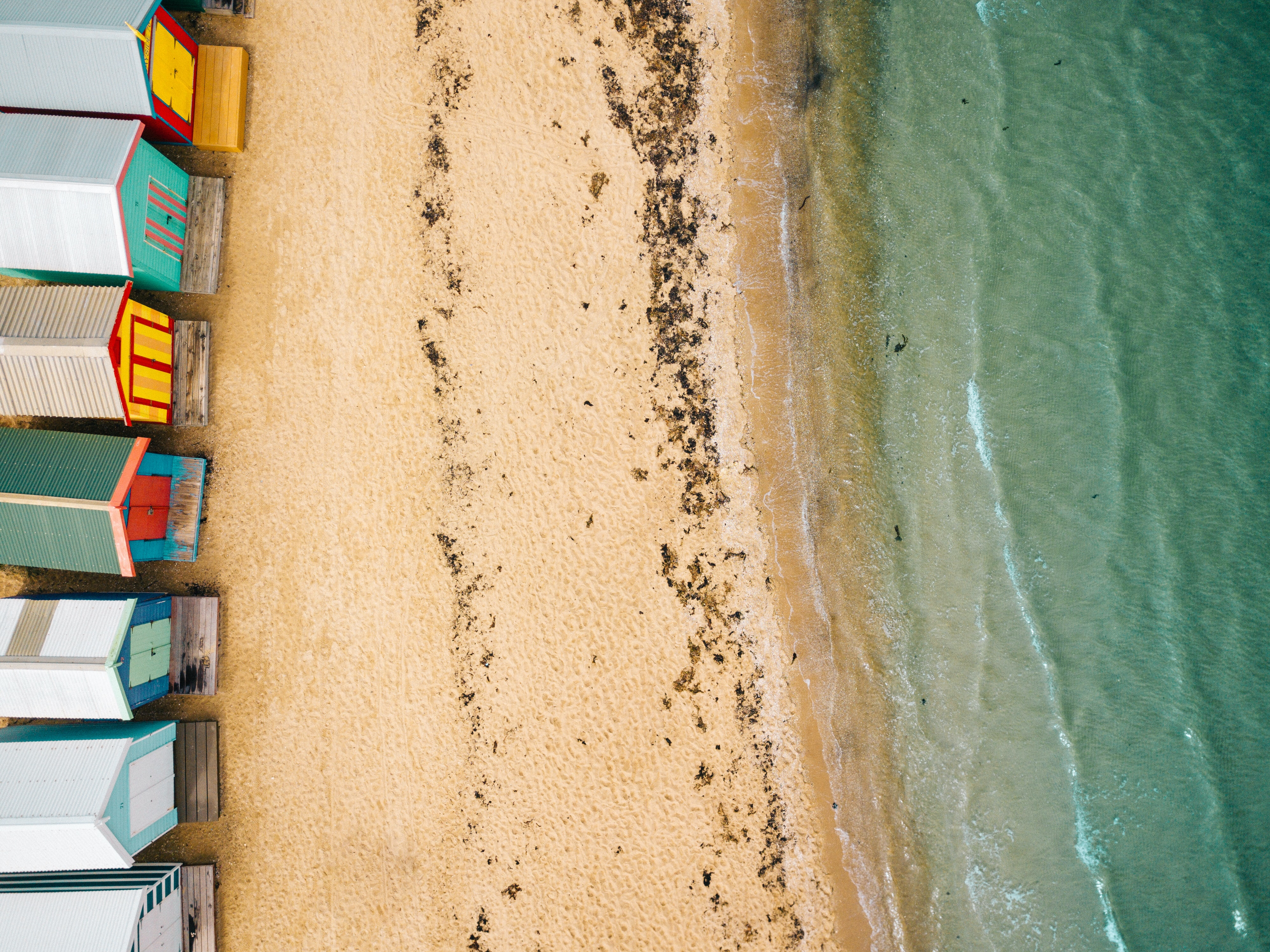Looking down on Brighton Beach and colourful bathing boxes from above