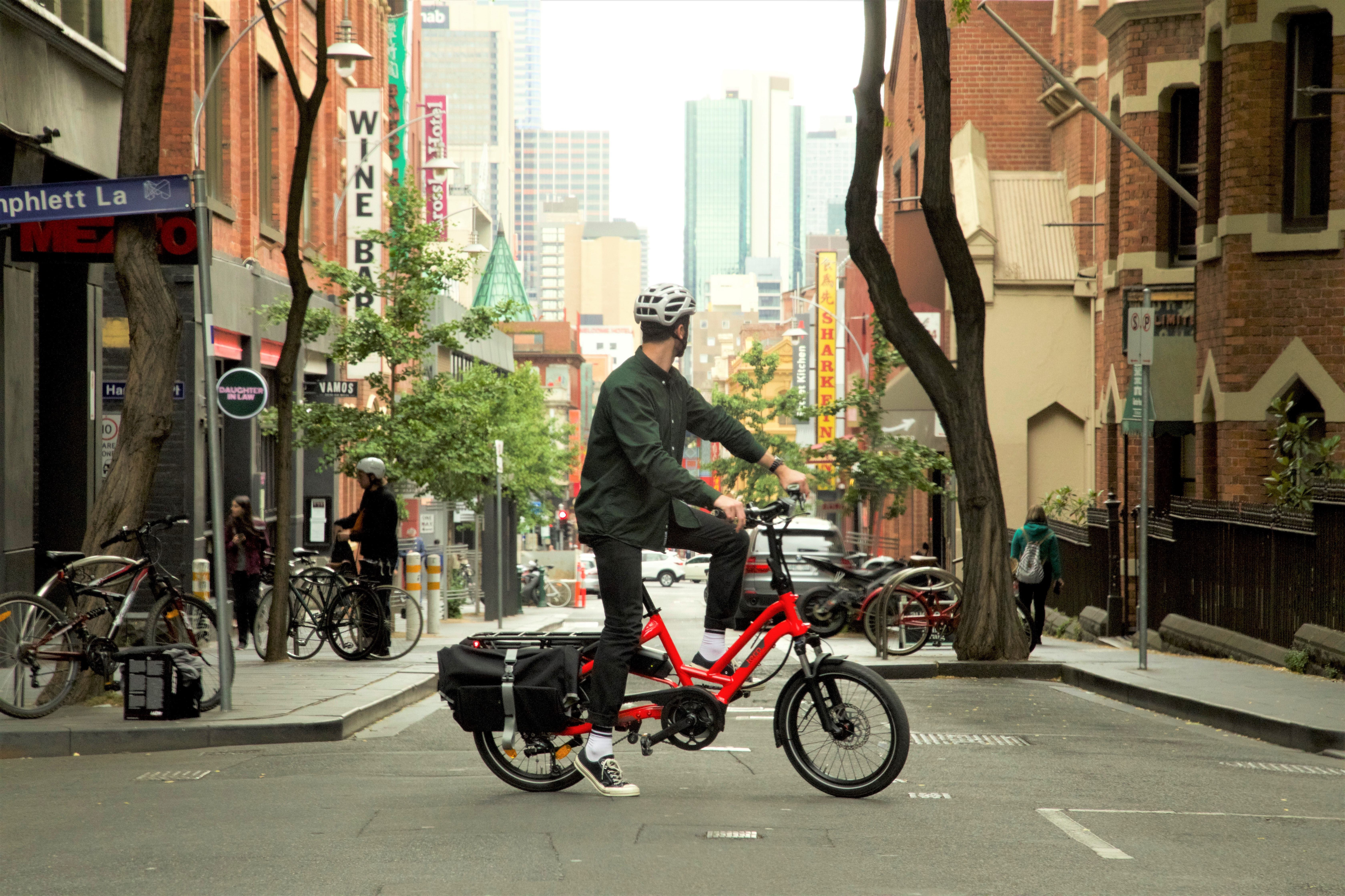 A man sits on a red Tern HSD in the middle of a Melbourne laneway