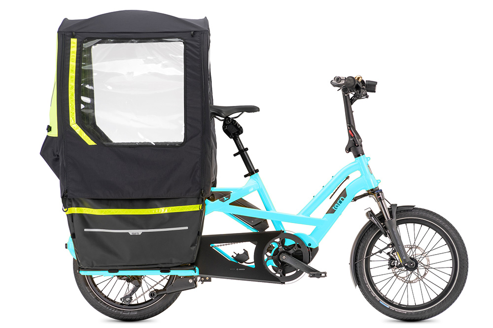 A blue Tern GSD electric cargo bike with a storm fort accessory