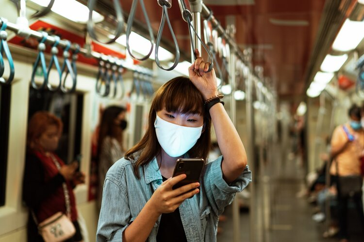 woman-wearing-a-face-mask-on-the-subway-and-using-her-4429307.jpg