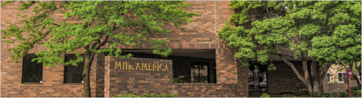 Brick building with trees and a Mid-America sign in front of it.