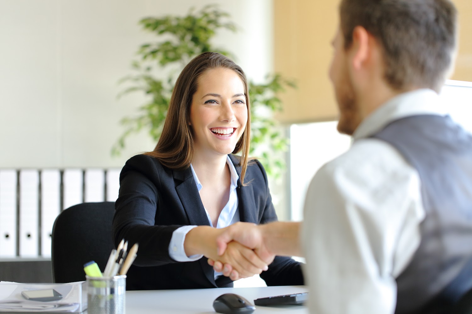 Types of interviews: Woman shakes hands with man