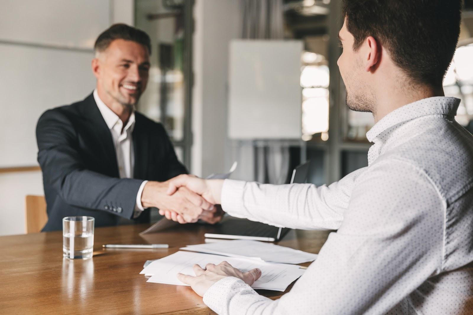 Employee retention strategies: Man shakes interviewee's hand