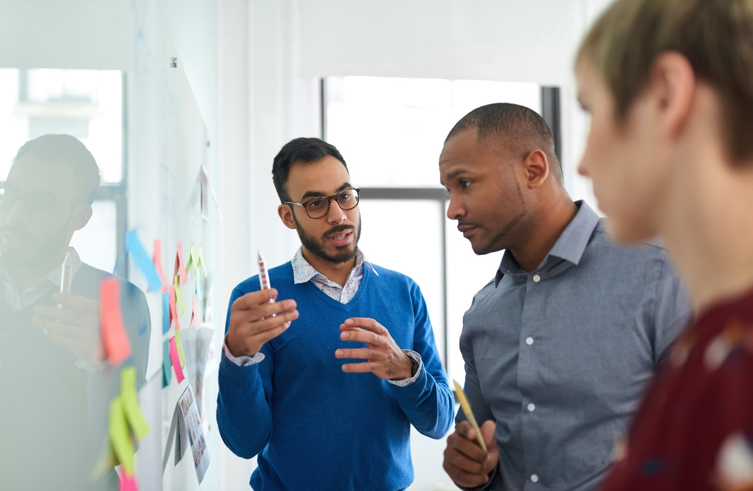 Competency-based interview: Team members brainstorm in front of a white board