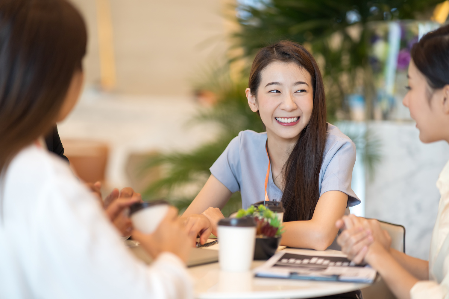 Onboarding best practices: Woman smiles while at lunch with co-workers