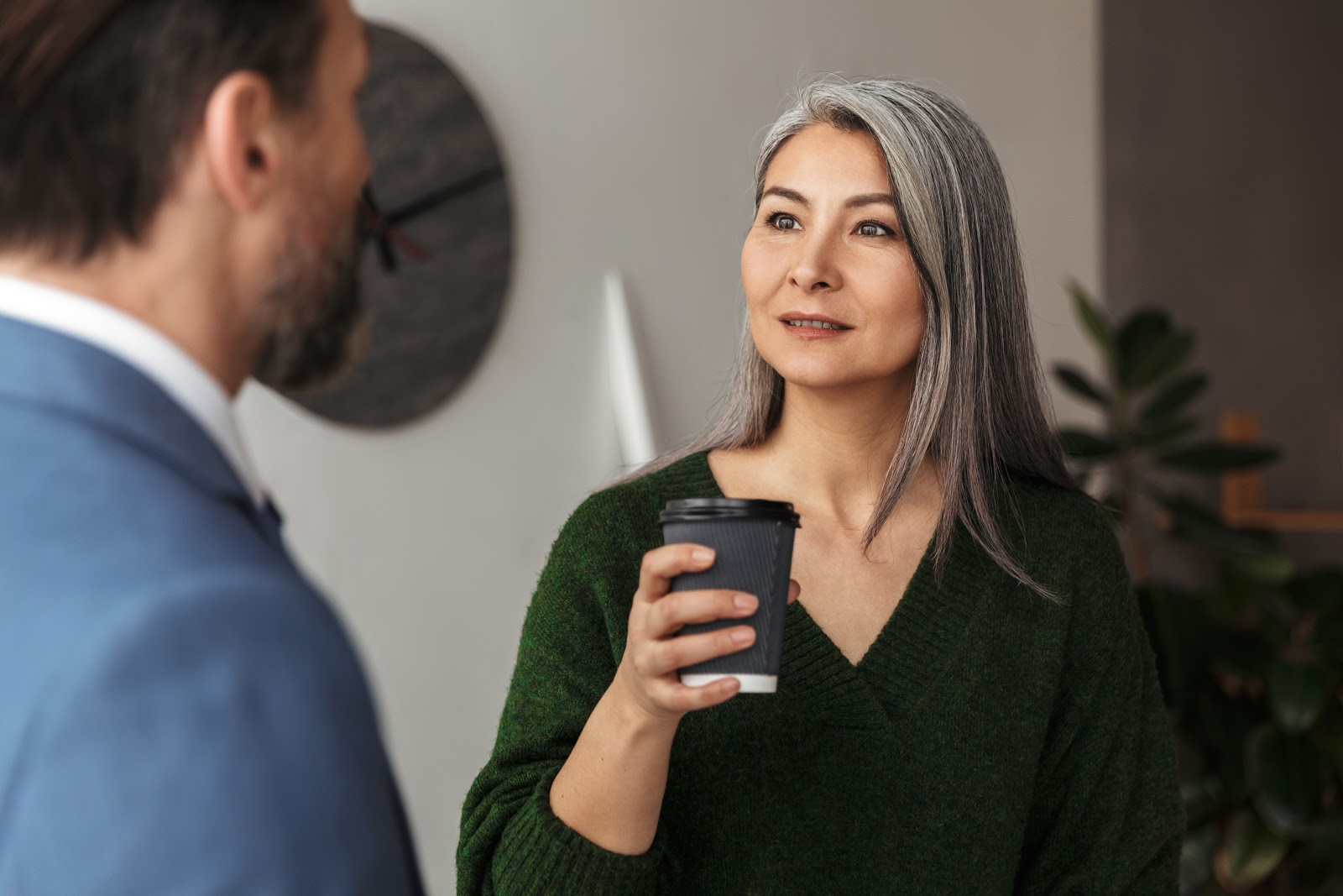Woman looks at colleague while holding cup of coffee