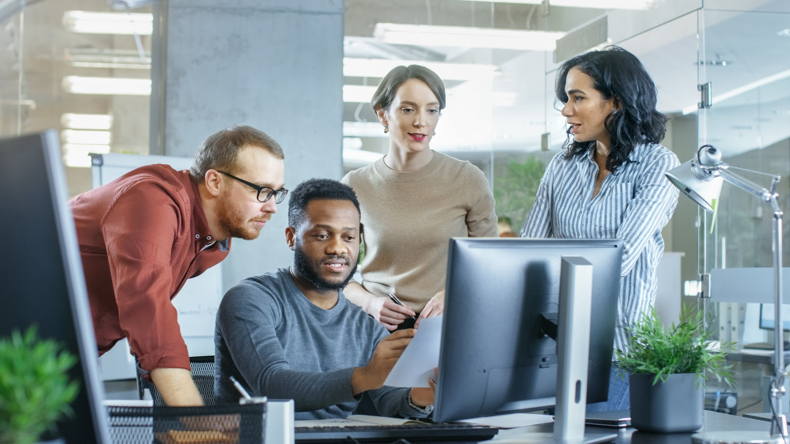 Group of diverse co-workers gathered around computer