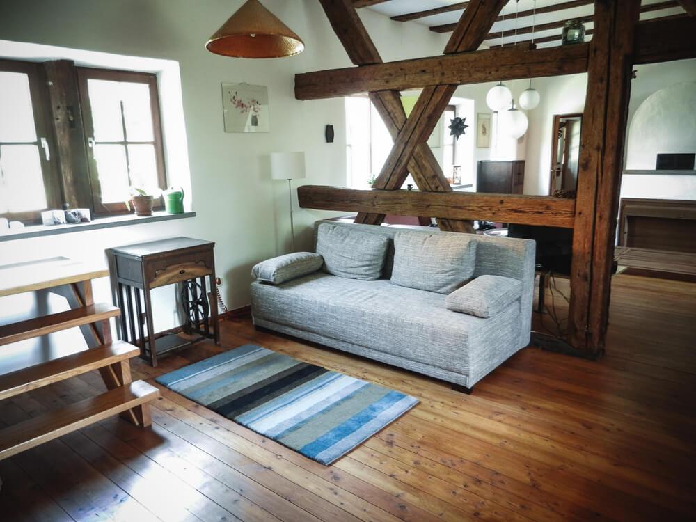 Das Wohnzimmer der Schäferei mit ausklappbarer Schlafcouch und Fenster in den Hof