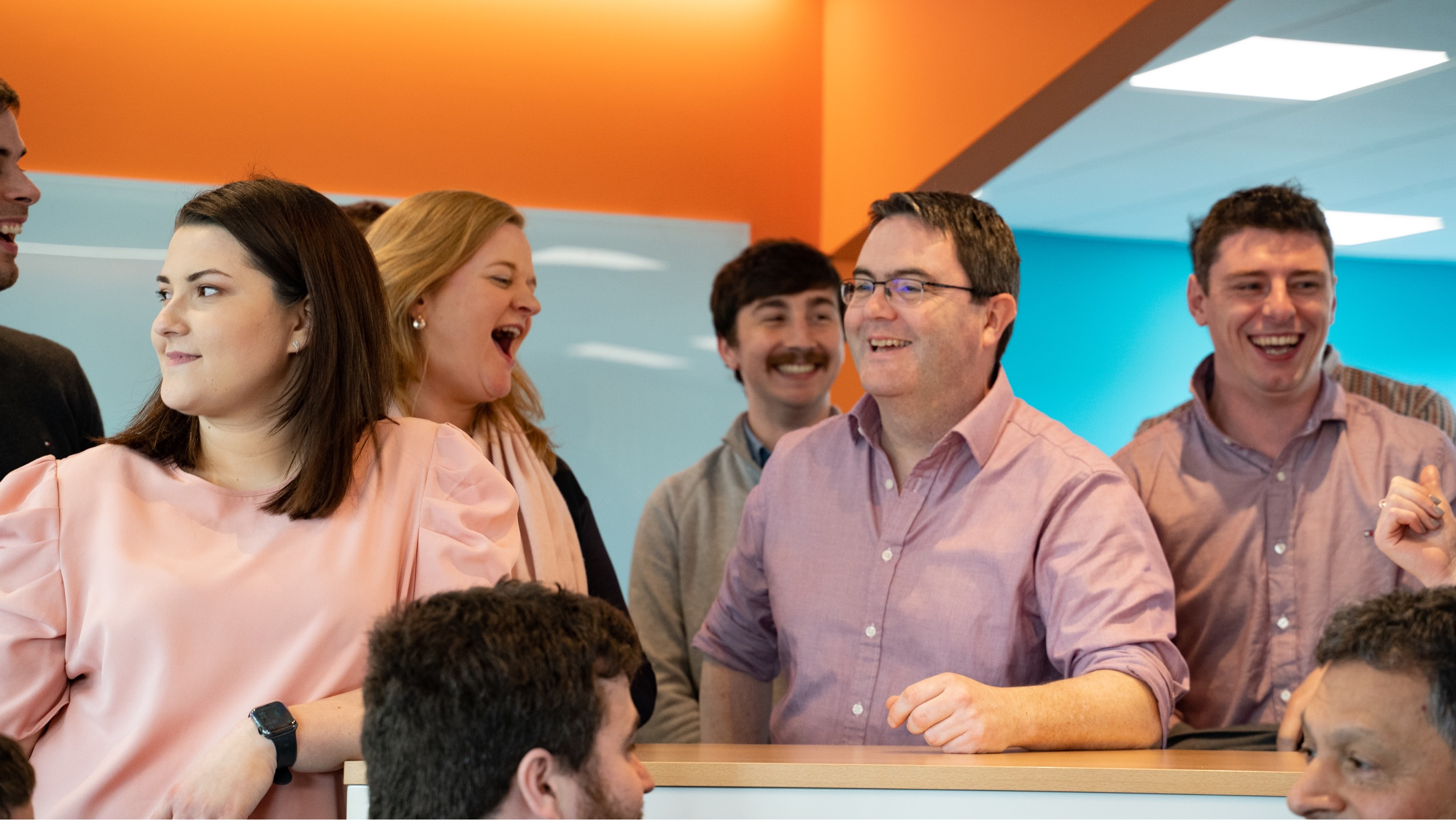 Members of the threefold team grouped together and they are smiling after Mike told a joke.
