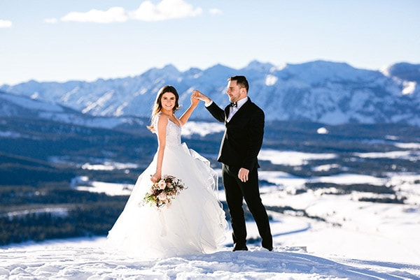 Bride and groom dancing on snowy mountain