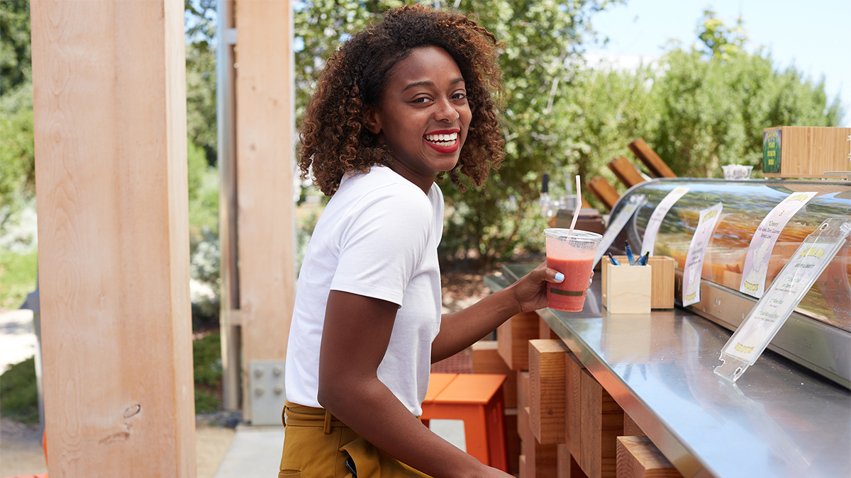 Smiling woman drinking a smoothie.