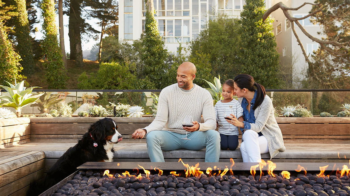 Family sitting around a fire pit.