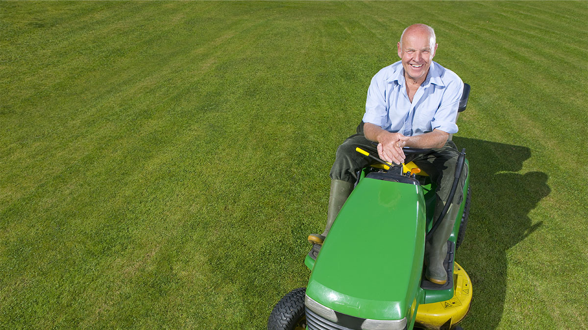 Older man posed on a lawn mower.