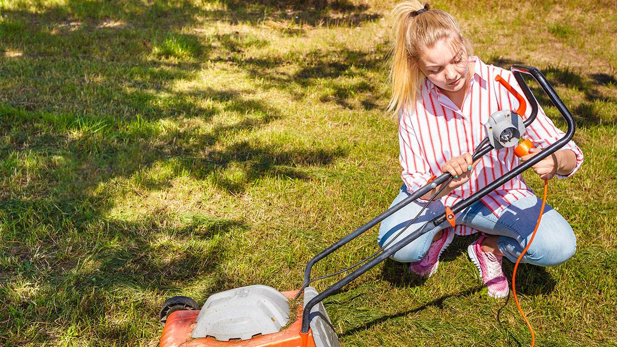 Woman fixing lawn mower in yard.