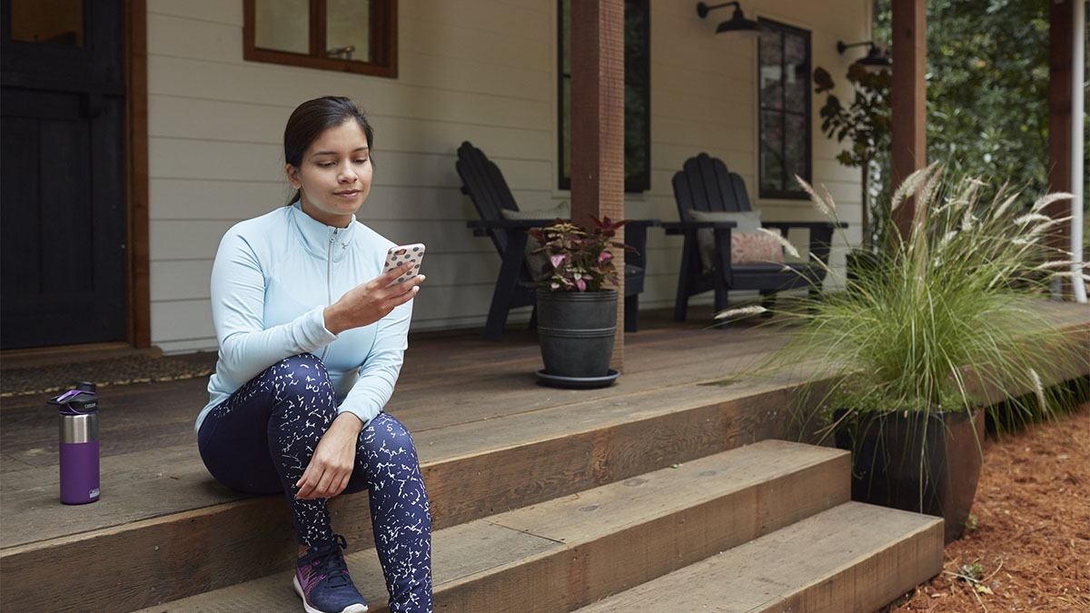 Young woman sitting on porch with phone.