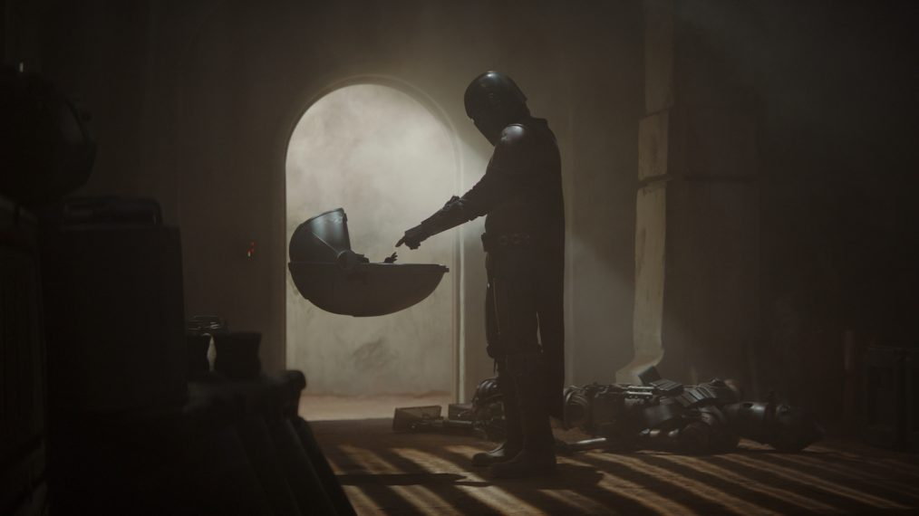 The Mandalorian and Baby Yoda in the first episode of the Mandalorian when he and Baby Yoda first meet. The Mandalorian is holding out a finger to the baby in the floating cradle and Baby Yoda is reaching to grasp The Mandalorain's hand