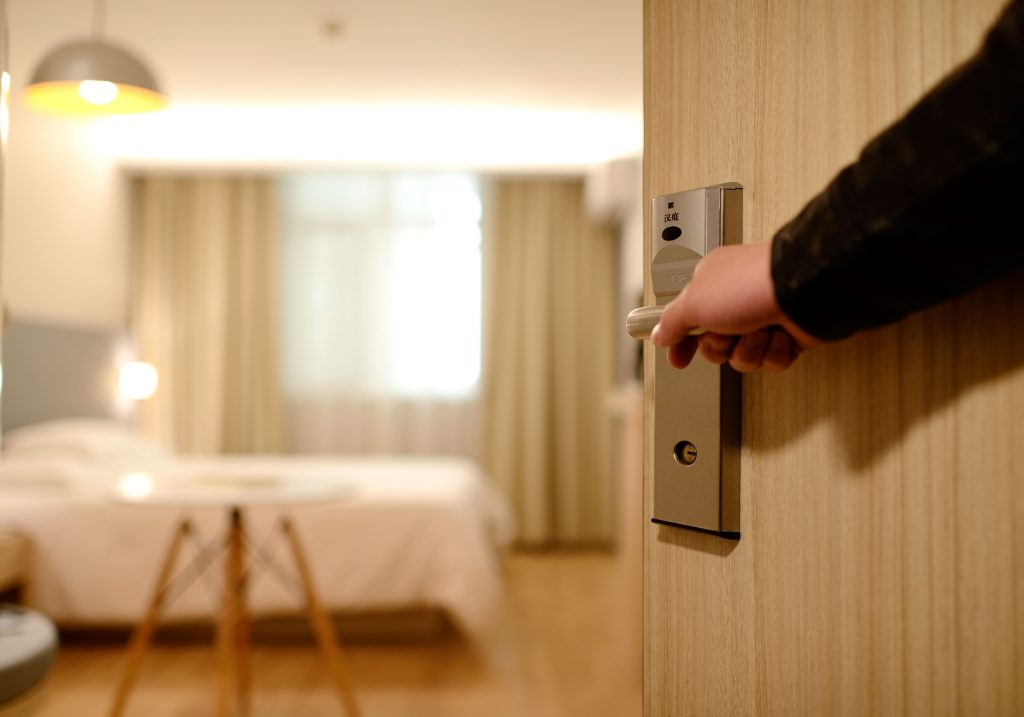 A hotel employee opens a room door for a customer. The room consists of neutral tans and creams from the bed, to the circular, three legged table, and the drapes. The hotel employee is demonstrating great customer experience.