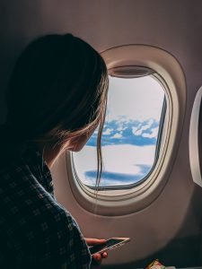 A young woman customer sits at a window seat on an airplane looking out at the snowy mountains. Airlines have the benefit of having naturally wonderful scenes to look at during the flight. An element of customer experience they don't have to work for.