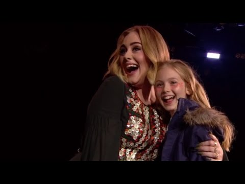 Adele poses with a young female fan.