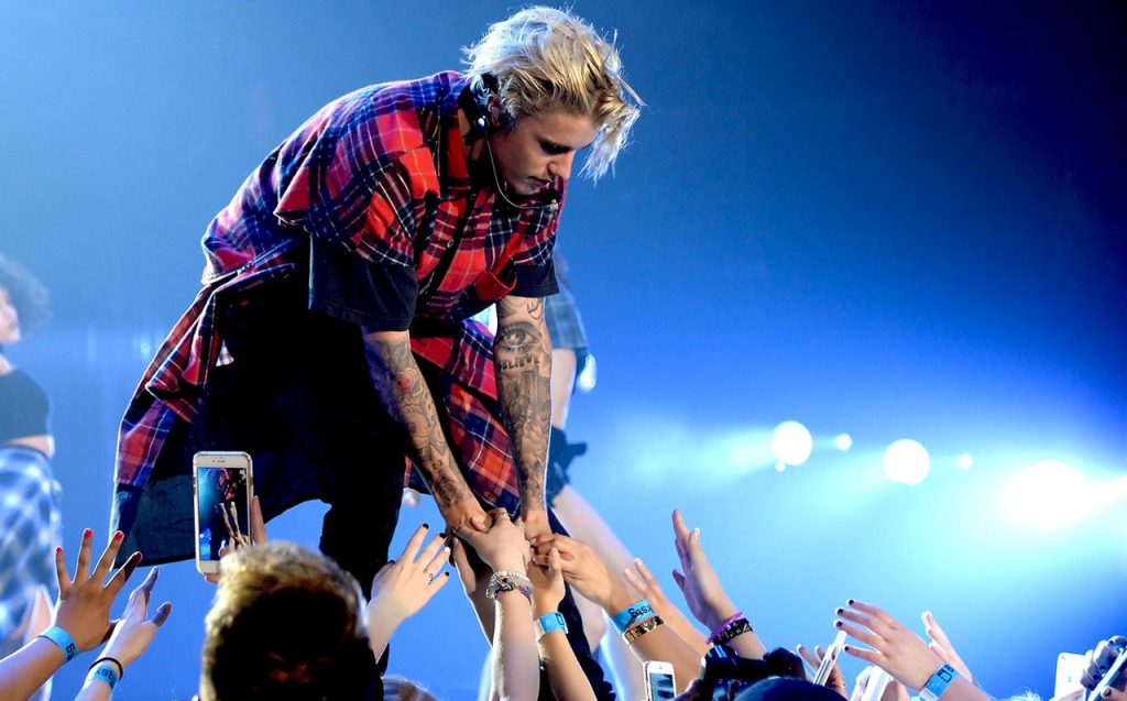 Justine Bieber leans down to hold the hands of a fan. Several more reach out, trying to touch him. Justin is in concert. He is wearing a red and black plaid shirt and tattooed arms. Justin always focused a lot on his fans, knowing that they are what make him successful.